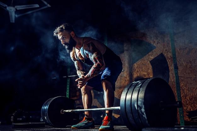 Hombre de la aptitud muscular que se prepara para el peso muerto de una barra en el gimnasio moderno. entrenamiento funcional.