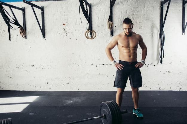 Hombre apto para entrenamiento de barra en el gimnasio