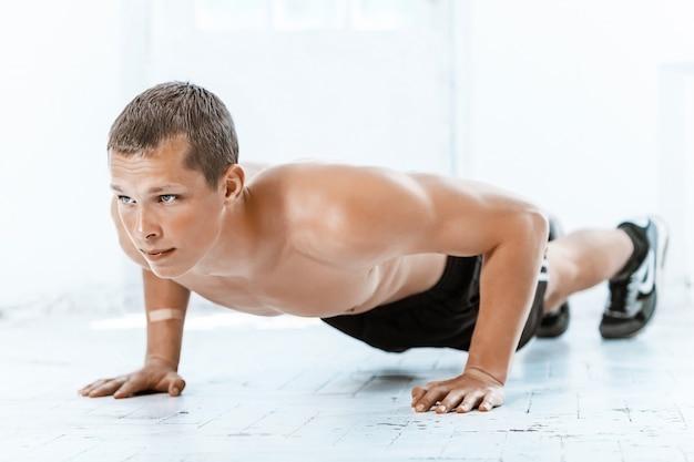Hombre apto haciendo algunas flexiones en el gimnasio