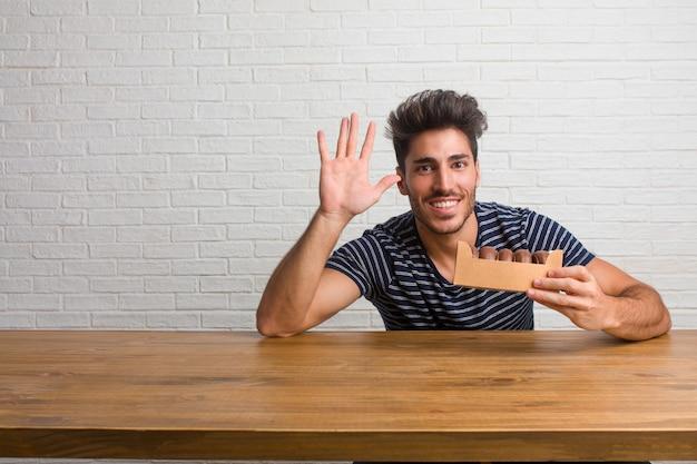 Hombre apuesto y natural joven sentado en una mesa que muestra el número cinco, símbolo de conteo