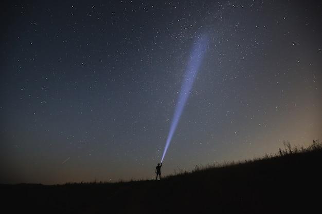 El hombre apunta con la linterna al cielo nocturno. noche de verano.