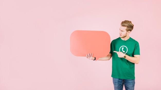 Hombre apuntando al bocadillo de diálogo naranja vacío sobre fondo rosa