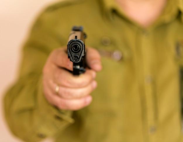 Hombre apuntando arma al blanco con una mano