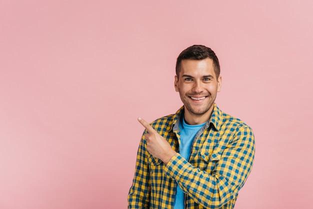 Hombre apuntando hacia arriba con fondo rosa