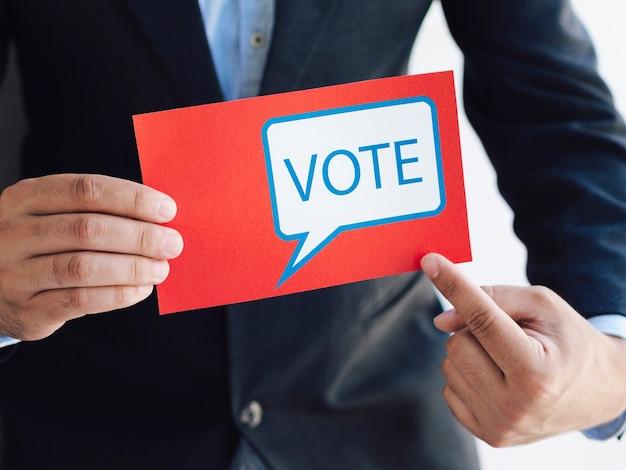 Hombre apuntando a una boleta con un mensaje de votación