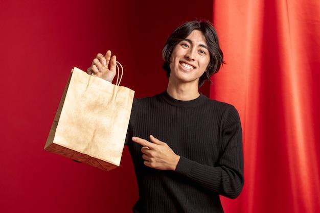 Hombre apuntando a la bolsa de compras para el año nuevo chino