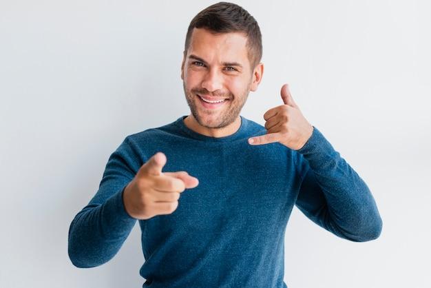 Hombre apuntando a la cámara con señal de llamada de mano
