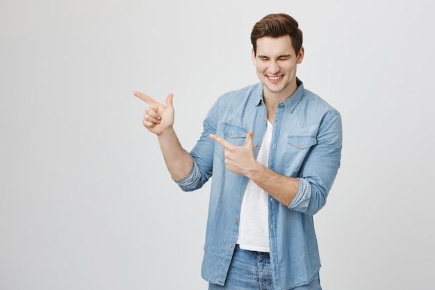 Hombre apuntando a la izquierda en pancarta divertida, riendo