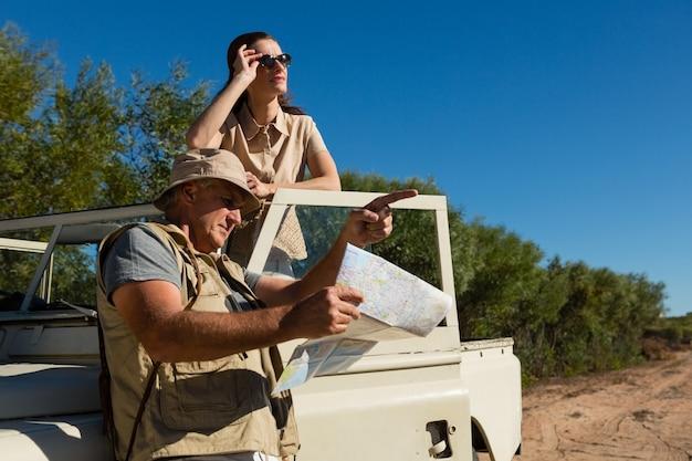 Hombre apuntando mientras sostiene el mapa con mujer en vehículo