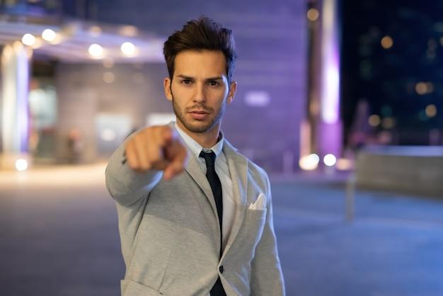Hombre apuntando con su dedo hacia usted en un entorno de ciudad nocturna