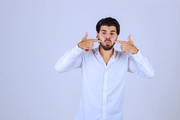 Hombre apuntando su nariz con ambos dedos.