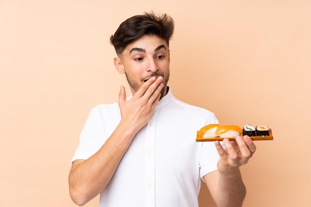 Hombre árabe comiendo sushi en pared beige con expresión facial sorprendida y conmocionada