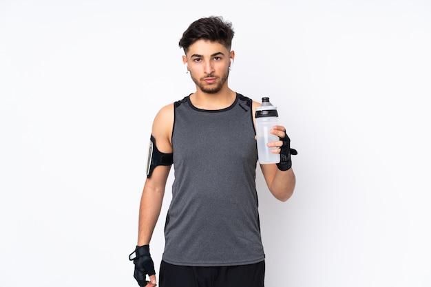 Hombre árabe deporte aislado en la pared blanca con botella de agua deportiva