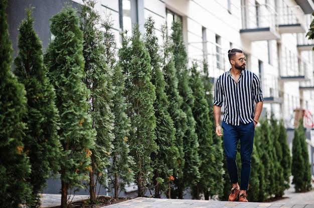 Hombre árabe exitoso en camisa a rayas y gafas de sol posan al aire libre.