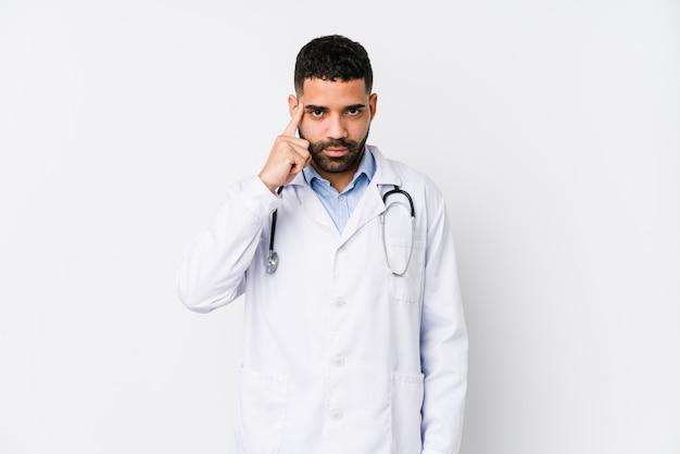 El hombre árabe joven del doctor aisló señalar el templo con el dedo, pensando, centrado en una tarea.