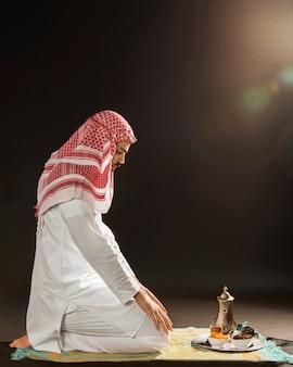 Hombre árabe con kandora rezando