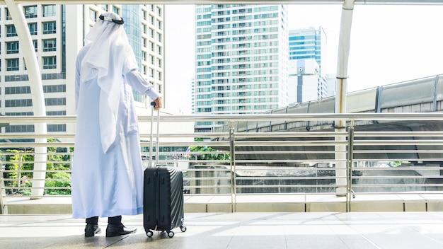 Hombre árabe lleva una maleta en la ciudad de negocios