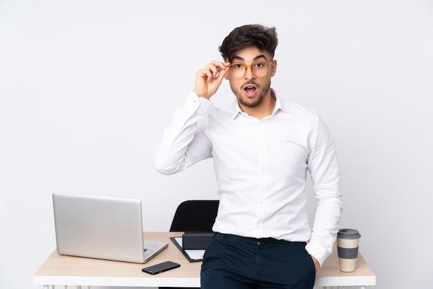 Hombre árabe en una oficina aislada en blanco con gafas y sorprendido