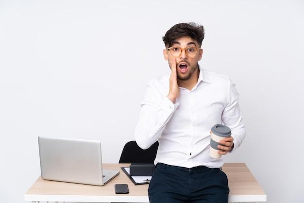 Hombre árabe en una oficina aislada en blanco con sorpresa y expresión facial conmocionada