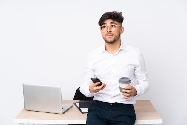 Hombre árabe en una oficina en la pared blanca con café para llevar y un móvil mientras piensa algo