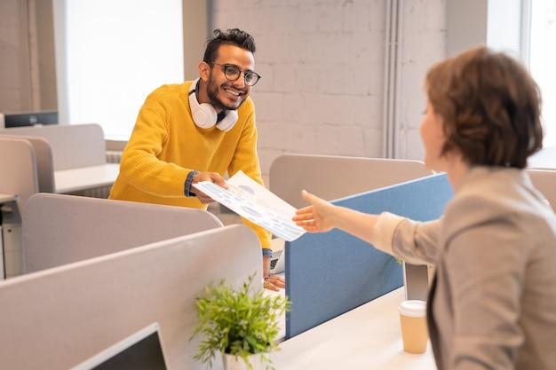 Hombre árabe positivo con auriculares en el cuello de pie en el escritorio en la oficina de espacios abiertos y dando documentos financieros a un colega