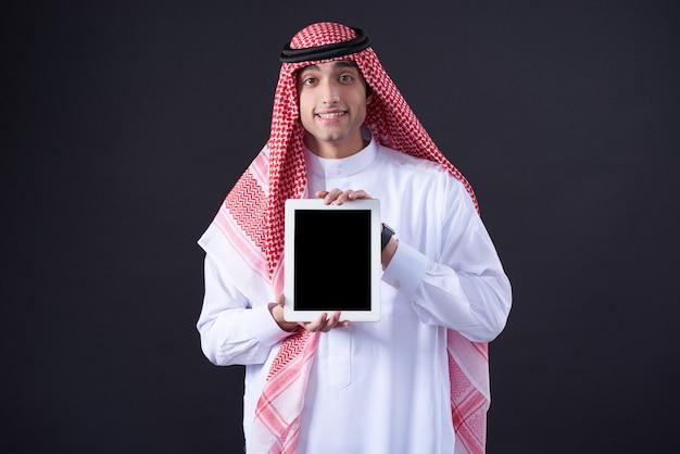 Hombre árabe que presenta con la tableta negra aislada.