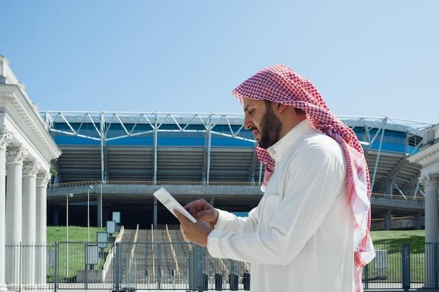 Hombre árabe rico sonriente comprando bienes raíces en la ciudad