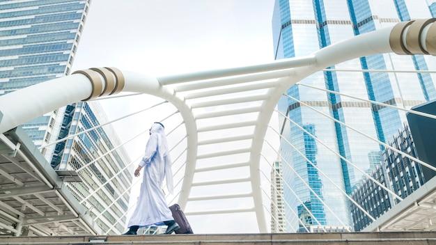 Hombre árabe del viajero árabe del negocio que lleva una maleta