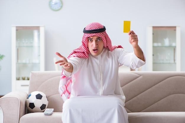 Hombre árabe viendo fútbol deportivo en la televisión