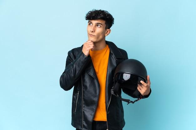 Hombre argentino con un casco de moto y mirando hacia arriba