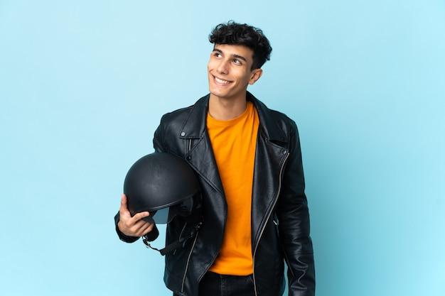 Hombre argentino con un casco de moto pensando en una idea mientras mira hacia arriba