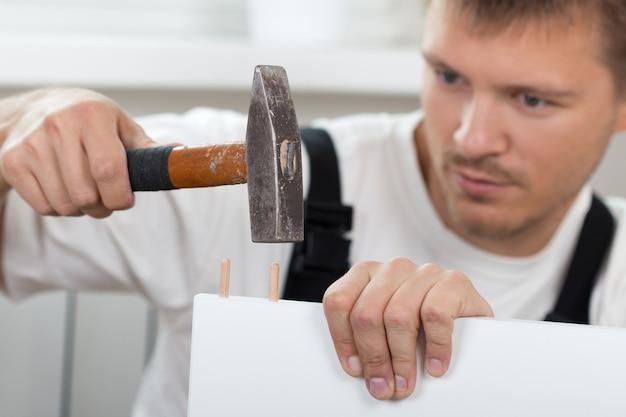 Hombre armando muebles de autoensamblaje en casa nueva de cerca. bricolaje, hogar y concepto de mudanza
