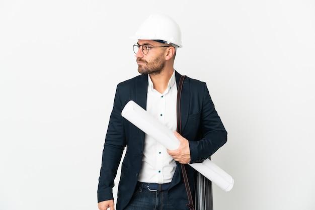Hombre arquitecto con casco y sosteniendo planos aislado sobre fondo blanco mirando hacia el lado