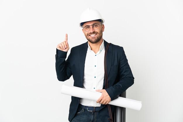 Hombre arquitecto con casco y sosteniendo planos aislados en blanco apuntando hacia una gran idea
