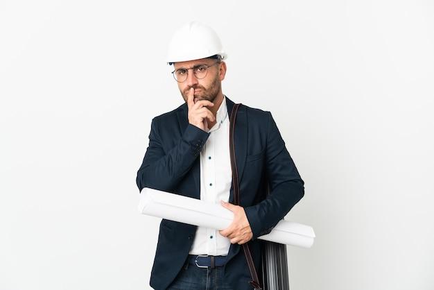 Hombre arquitecto con casco y sosteniendo planos aislados en blanco con dudas mientras mira hacia arriba