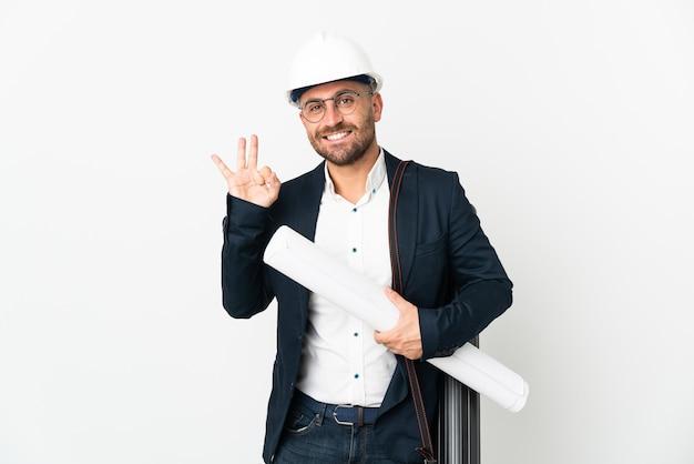 Hombre arquitecto con casco y sosteniendo planos aislados en blanco mostrando signo ok con los dedos