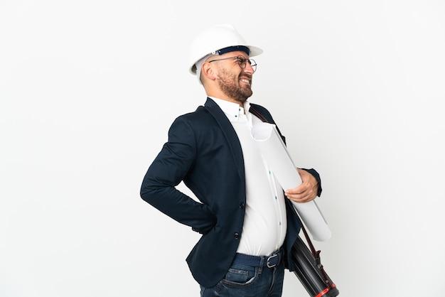 Hombre arquitecto con casco y sosteniendo planos aislados en blanco que sufren de dolor de espalda por haber hecho un esfuerzo