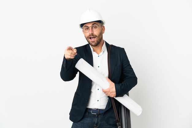 Hombre arquitecto con casco y sosteniendo planos aislados en blanco sorprendido y apuntando hacia el frente