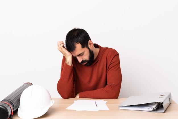 Hombre de arquitecto caucásico con barba en una mesa con dolor de cabeza.