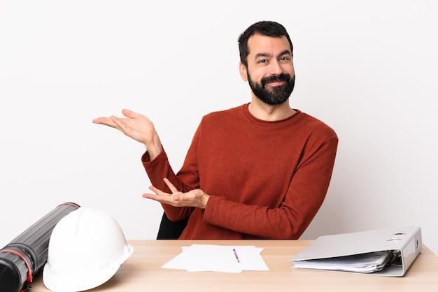 Hombre de arquitecto caucásico con barba en una mesa extendiendo las manos hacia un lado para invitar a venir.