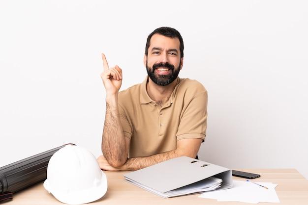 Hombre de arquitecto caucásico con barba en una mesa feliz y apuntando hacia arriba.