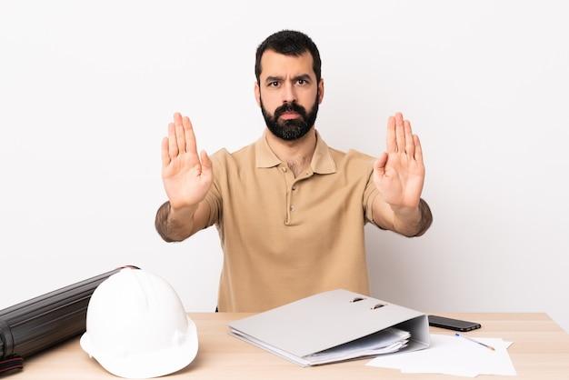 Hombre de arquitecto caucásico con barba en una mesa haciendo gesto de parada y decepcionado