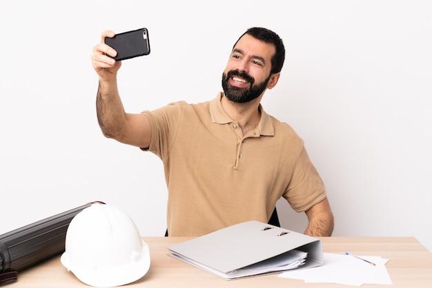 Hombre de arquitecto caucásico con barba en una mesa haciendo un selfie.