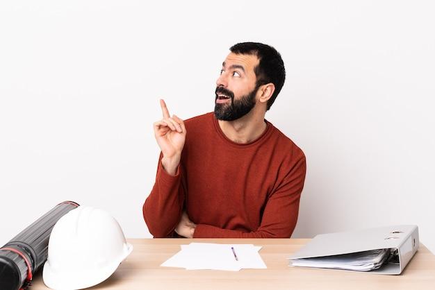 Hombre de arquitecto caucásico con barba en una mesa pensando en una idea apuntando con el dedo hacia arriba.