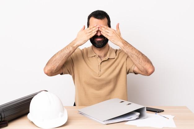 Hombre de arquitecto caucásico con barba en una mesa que cubre los ojos con las manos y sonriendo.