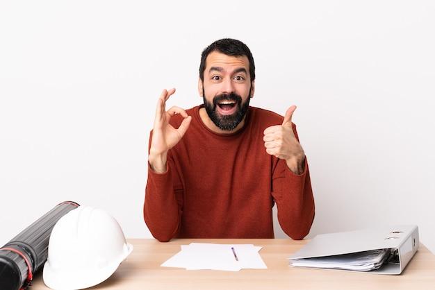 Hombre de arquitecto caucásico con barba en una mesa que muestra el signo de ok y el pulgar hacia arriba gesto.