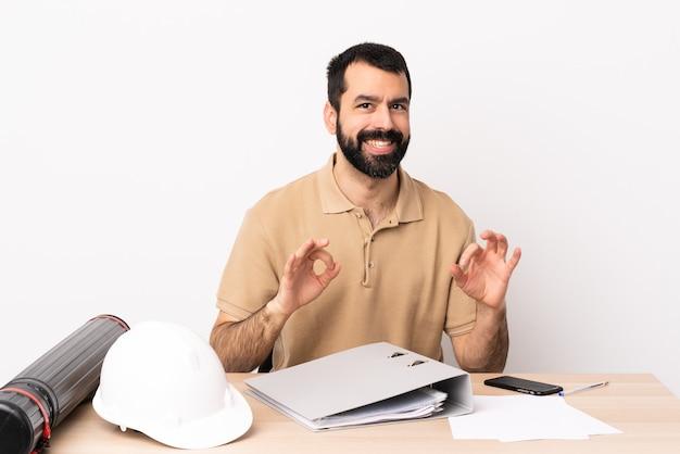 Hombre de arquitecto caucásico con barba en una mesa que muestra el signo de la victoria con ambas manos.