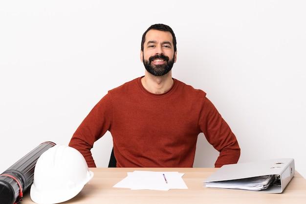 Hombre de arquitecto caucásico con barba en una mesa riendo.