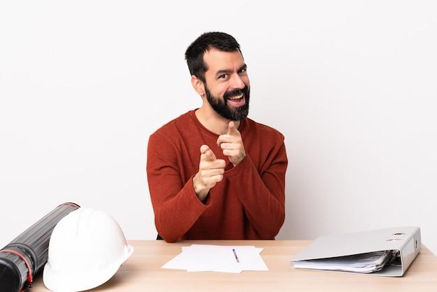 Hombre de arquitecto caucásico con barba en una mesa sorprendido y apuntando al frente.
