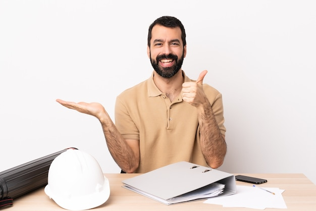 Hombre de arquitecto caucásico con barba en una mesa sosteniendo copyspace imaginario en la palma para insertar un anuncio y con el pulgar hacia arriba.